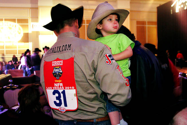 World champion Dean Gorsuch holds his son Trell during the NFR World Champion Awards Show and After Party at The Mirage on Saturday, Dec. 11, 2010.