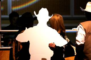 A rodeo fan carries a cardboard cutout of a PRCA cowboy up to the bar at the NFR World Champion Awards Show and After Party at the Mirage Saturday, December 11, 2010.