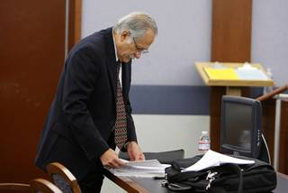 Edward Preciado-Nuno looks over paperwork during a break in his murder trial at the Regional Justice Center Thursday, December 16, 2010. Preciado-Nuno, a retired FBI special agent, is accused of killing his son's girlfriend Kimberly Long. Preciado-Nuno says he was attacked by the girlfriend and killed her in self-defense.