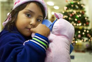 Evelin Camarena, 4, holds new toys at Catholic Charities of Southern Nevada Thursday, December 16, 2010. The Catholic Charities program provided free toys, jackets and other clothing for low-income families.