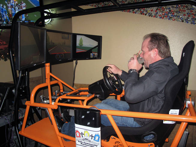 John Dlouhy takes a sip of a drink while driving a simulator at the T-Bird Lounge on Eastern Avenue Friday to demonstrate the effects alcohol has on driving. Police are planing extra patrols and DUI checkpoints over the next two weeks for the holidays.