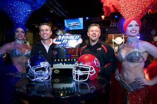 Boise State coach Chris Petersen, left, and Utah coach Kyle Whittingham pose with showgirls during a news conference at the Hard Rock Cafe on the Las Vegas Strip Sunday, December 19, 2010. Utah is scheduled to face Boise State in the MAACO Bowl Las Vegas NCAA college football game at Sam Boyd Stadium on Wednesday.