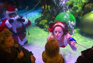 One of Santa's helpers puckers up for a kiss as children visit with an underwater Santa Claus swimming in a 117,000-gallon aquarium at the Silverton hotel-casino Sunday, December 19, 2010. Santa was equipped with a microphone so that he could communicate with the children.
