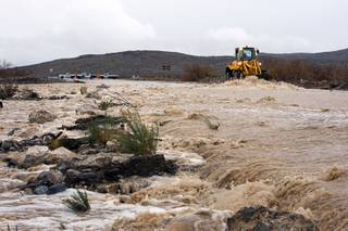 A Nevada Department of Transportation front loader keeps debris from building up as rain run-off washes over the roadway on State Route 159 near Calico Basin Dec. 22, 2010.