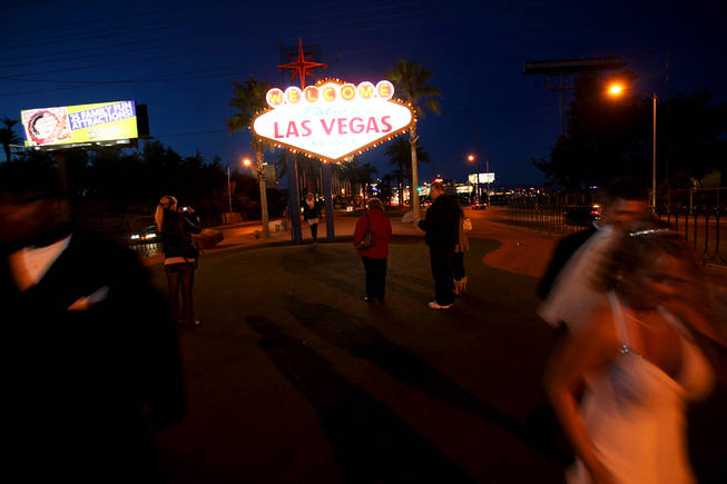 "A newlywed couple leaves as people wait their turn to get photos at the ""Welcome to Fabulous Las Vegas"" sign on New Year's Eve 2010."