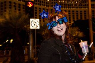 A partygoer wearing festive glasses starts the celebration on New Year's Eve 2010.