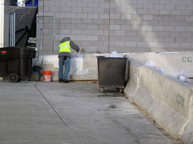 A worker picks up trash near Planet Hollywood on the Las Vegas Strip early on New Year's Day.
