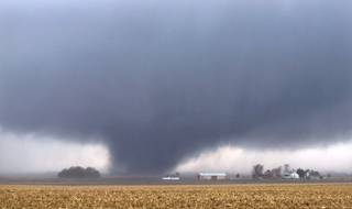 A tornado 2 miles west of Flatville, Ill., moves northeast at 12:51pm. The tornado damaged many farm buildings and homes on its way to Gifford, Ill., where scores of houses were devastated.  (AP Photo/News-Gazette/Jessie Starkey) MANDATORY CREDIT