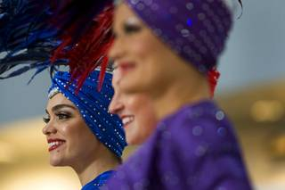 Showgirl Porsha Revesz, left, listens to speakers during the unveiling of a 627-square-foot video wall in the D Concourse rotunda of McCarran International Airport Monday, Jan. 3, 2011.