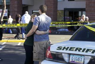 Two people embrace each other at the scene where Rep. Gabrielle Giffords, D-Ariz., and others were shot outside a Safeway grocery store in Tucson, Ariz. on Saturday, Jan. 8, 2011.