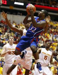 In this Jan. 12, 2011, file photo, Kansas guard Josh Selby (32) shoots over Iowa State forward Jamie Vanderbeken (23), forward Melvin Ejim and guard Jake Anderson (5) during the first half of an NCAA college basketball game in Ames, Iowa.