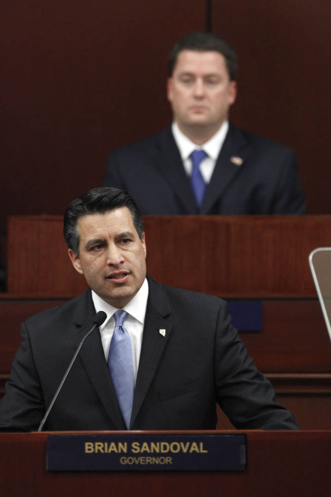 Gov. Brian Sandoval makes his first State of the State address before a joint session of the Nevada Legislature as Assembly Speaker-elect John Oceguera, D-Las Vegas, background, looks on, in Carson City on Monday, Jan. 24, 2011.