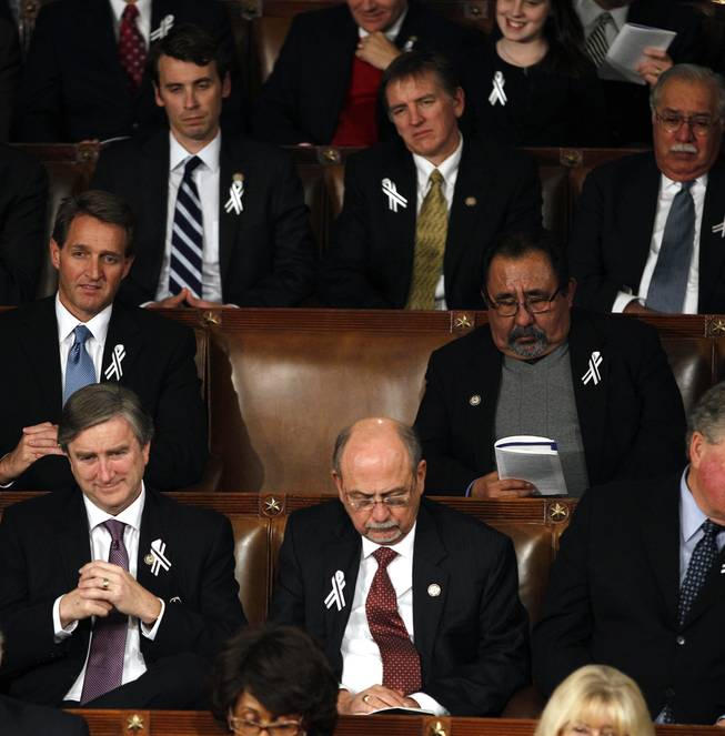 An empty seat for Rep. Gabrielle Giffords, D-Ariz. is seen on Capitol Hill in Washington, Tuesday, Jan. 25, 2011, during President Barack Obama's State of the Union address. Rep. Jeff Flake, R-Ariz. is at left, Rep. Raul Grijalva, D-Ariz. is at right.