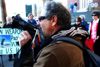 Jim Haber, Coordinator of the Nevada Desert Experience, joins in a protest with members of the Creech 14, a group of people who were arrested in April 2009 for protesting the use of remote-controlled Predator drones at the Creech Air Force Base, protests outside of Clark County Regional Justice Center Thursday, Jan. 27, 2011 just before their decision was read.