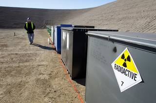 A worker walks by containers of mixed waste in the Area 5 Radioactive Waste Management Site of the Nevada National Security Site (N2S2), previously the Nevada Test Site, about 65 miles northwest of Las Vegas on Feb. 1, 2011.