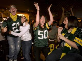 Green Bay Packers fans celebrate a touchdown against the Steelers as they watch Super Bowl XLV at the Rum Runner, 1801 E. Tropicana Ave., February 6, 2011. From left are Kyle Drodny, Alicai Williams, Jessica Buscemi, and Samantha Mentzel.
