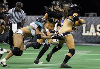 Marirose Roach, left, of the Philadelphia Passion puts the pressure on quarterback Ashley Salerno of the Los Angeles Temptation during the Lingerie Bowl VIII at the Thomas & Mack Center Sunday, Feb. 6, 2011. The event was a pay-per-view show that could be ordered at half-time of Super Bowl XLV. The Las Vegas Sin, an expansion team, will join the Lingerie Football League this fall.