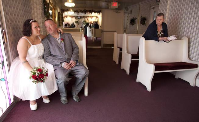 Amanda, left, and Albert Burton wait for receive their marriage certificate as Mona Burton, Albert's mother, looks on after the two married at the Little White Wedding Chapel, Monday, Feb. 14, 2011 in Las Vegas.