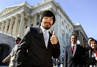 Boxing superstar and Filipino Congressman Manny Pacquiao poses in front of  the Senate Building on Capitol Hill after meeting with Senate Majority leader Harry Reid (D-NV) today in Washington D.C. as part of a goodwill tour February 15, 2011.