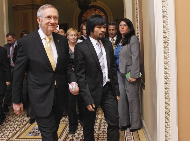 Senate Majority Leader Harry Reid of Nev., left, walks with Filipino Congressman and eight-time world champion boxer Manny Pacquiao on Capitol Hill in Washington, Tuesday, Feb. 15, 2011.