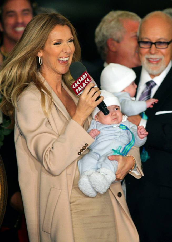 Celine Dion speaks to employees, reporters and fans as she arrives at Caesars Palace with her husband and sons on Feb. 16, 2011. Dion is holding her son Nelson. Her husband Rene Angelil is holding twin brother Eddy. The singer begins a new series of shows at The Colosseum at Caesars Palace on March 15.