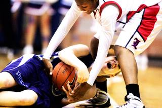 Cheryl Harless of Foothill, bottom, fights for the ball with Liberty's Alena Evans during the Sunrise Regional girls basketball championships at Foothill High School in Henderson Friday, February 18, 2011.