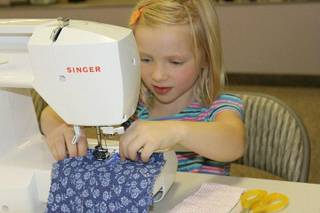 Georgia Deibert, 6, perfects her sewing skills during a class at Little Hip Chix Studio.