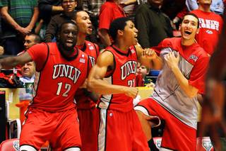 UNLV players Brice Massamba, Chace Stanback, Justin Hawkins and Karam Mashour celebrate taking the lead late against New Mexico during Wednesday's Mountain West Conference game at The Pit in Albuquerque. UNLV won 77-74 in overtime.