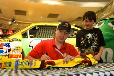 NASCAR driver Kyle Busch signs a jacket for Tristen MacLean, 11, of Carseland, Alberta, Canada at the M&M's World Las Vegas store on the Las Vegas Strip Thursday, March 3, 2011.