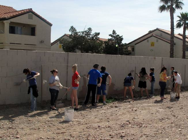 Students from the youth program at the Crossing Christian Church paint over graffiti Saturday near U.S. 95 and Charleston Boulevard.