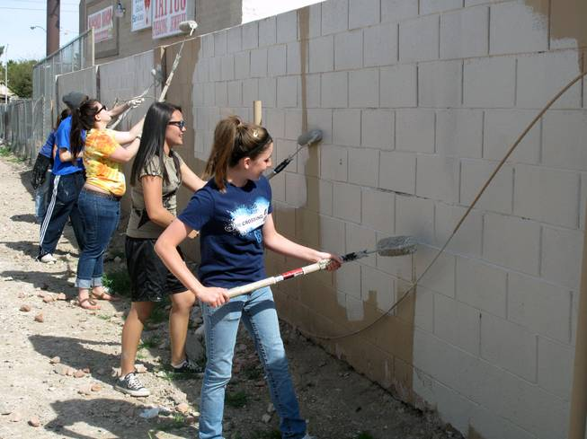 Ashlee Coate, right, and Chloe Jones, both 15, clean up graffiti Saturday morning near U.S. 95 and Charleston Boulevard along with other participants of a student ministry at the Crossings Christian Church.