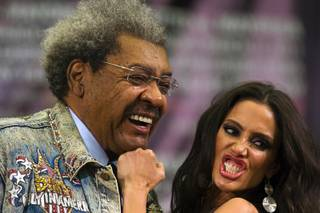 Boxing promoter Don King poses with Tecate Girl Janice KakIsh during a news conference at the MGM Grand Wednesday, March 9, 2011.