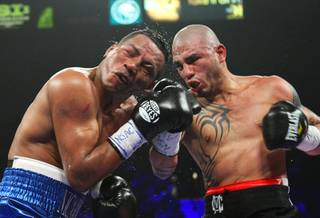 Ricardo Mayorga of Nicaragua (L) takes a punch from Miguel Cotto of Puerto Rico during their WBA world super welterweight title fight at the MGM Grand Garden Arena on March 12, 2011.