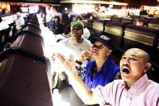 Thanomkeo Hanesana, right, and his wife, Jiamjit, of Las Vegas watch basketball games at the Race and Sports SuperBook at the Las Vegas Hilton Tuesday, March 15, 2011.