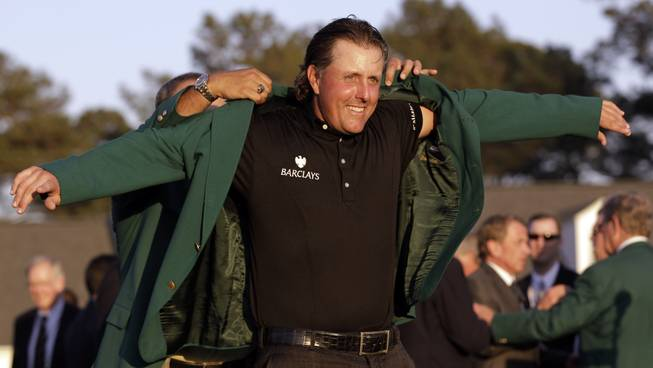Phil Mickelson slips into his green jacket after winning his third Masters championship last year at Augusta National in Augusta, Ga.
