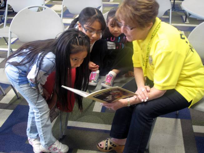 A Metro Police volunteer reads to children whose parents are attending the Hispanic Citizens Academy at the Pearson Community Center. Childcare is provided during the academy, which provides police an opportunity to foster good relationships with Hispanic children.