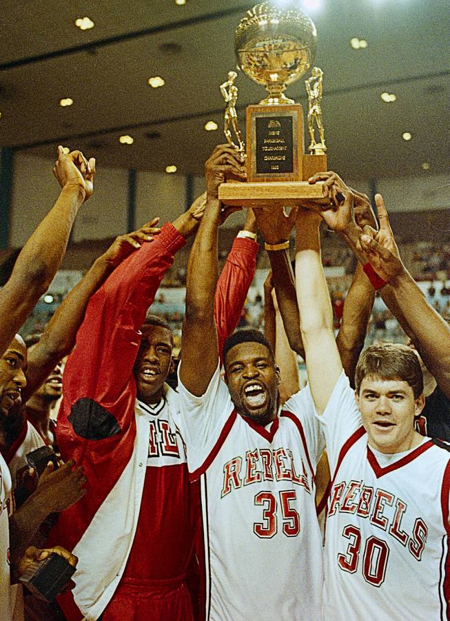 UNLV players hold their Big West trophy high over their heads in jubilation after beating California State University-Long Beach, to win the tournament in Long Beach, Calif., March 11, 1990.  Left to right are Barry Young, Moses Scurry (35) and Dave Rice.