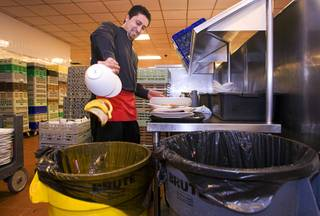 Buffet server Ismael Vidales empties food scaps into a yellow recycling bucket at the Mirage buffet kitchen Monday, April 12, 2011. The food scaps will go to feed pigs at R.C. Farms in North Las Vegas.