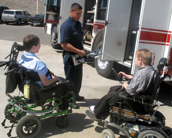 A Henderson firefighter shows 13-year-old Ian Preston, left, and 11-year-old Kyle Preston, right, tools the fire crews use while at emergency scenes. The brothers, who have Duchenne muscular dystrophy, attended the kickoff Tuesday of the 52nd annual Fill-the-Boot drive for the Muscular Dystrophy Association.