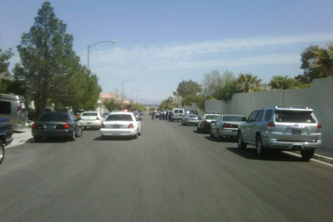 In this cellphone photo, Metro Police investigate an officer-involved shooting Tuesday, April 12, 2011, near Grand Canyon Drive and Alexander Road in the northwest valley.