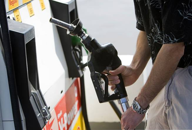 Kurtis Keeler of Jamestown, New York, replaces a pump after filling up at a gas station on Blue Diamond Road Thursday, April 14, 2011.