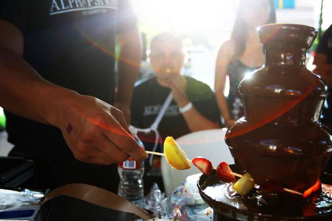 A member of the Alpha Psi Rho fraternity prepares a fruit kabob dipped in a chocolate fountain during UNLVs annual Festival of Communities on the UNLV campus Saturday, April 16, 2011.
