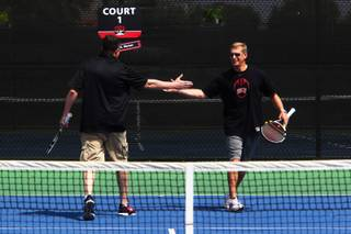 UNLV basketball coach Dave Rice (left) and football coach Bobby Hauck give each other high-fives during an exhibition tennis match with NCAA doubles champion Tim Blenkiron and one of his students, 10-year-old Jack Hambrook, at the Fertitta Tennis Complex on the UNLV campus Saturday, April 23, 2011.