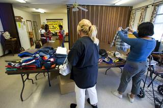 Recipients of the Fish Inc. program look over donated clothing at the Calvary Southern Baptist Church in North Las Vegas Wednesday, April 27, 2011. The program provides emergency food assistance to people who are struggling to get by.