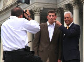 Sen. John Ensign has some fun with a staff member while taking office photographs on the steps of the Senate at the Capitol in Washington, D.C., on Thursday, April 28, 2011.