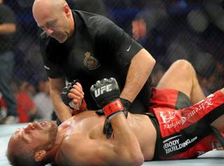 Randy Couture, bottom, attended to by the referee after being knocked out by Lyoto Machida during the light heavyweight bout at UFC 129 in Toronto on Saturday, April 30, 2011.