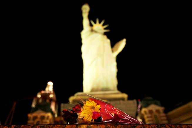 Flowers are left in front the Statue of Liberty at ...