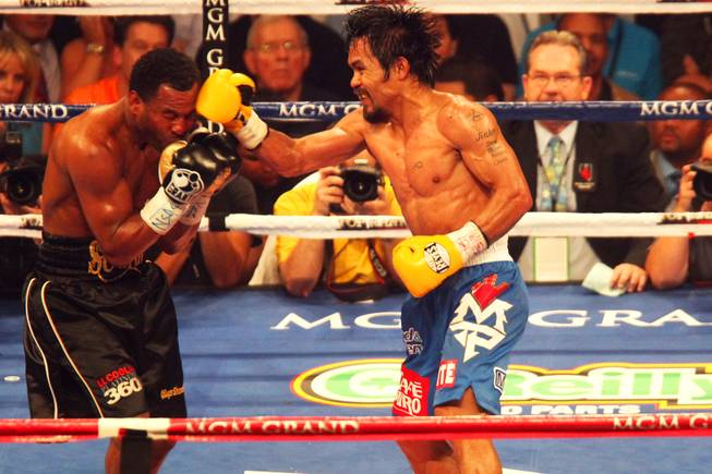 Shane Mosley takes a punch from Manny Pacquiao during their WBO welterweight title fight at the MGM Grand Garden Arena on May 7, 2011.