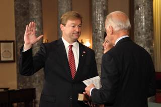 Sen. Dean Heller re-enacts taking the official Senate oath of office from Vice President Joe Biden in the Old Senate Chamber, with his wife Lynne holding a Bible, in the Capitol on May 9, 2011.