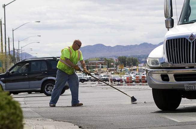 A Ewing Bros. tow operator sweeps up debris after an accident at Boulder Highway and Tropicana Avenue, May 17, 2011.